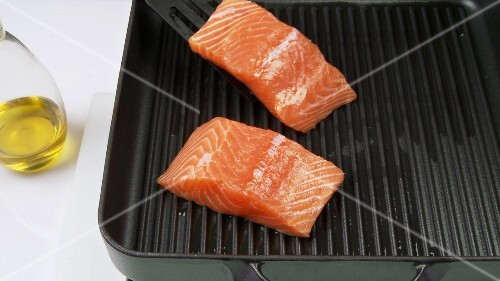 Cutting salmon fillet into pieces and frying it in a grill frying pan