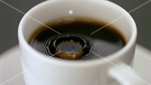 Drop of milk falling into a cup of coffee