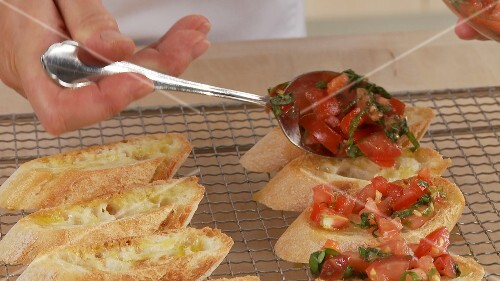 Preparing bruschetta: spreading the prepared tomatoes on the slices of bread