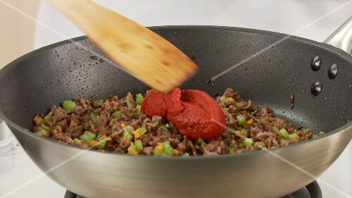 Tomato puree being added and stired into to a minced meat and vegetable mixture