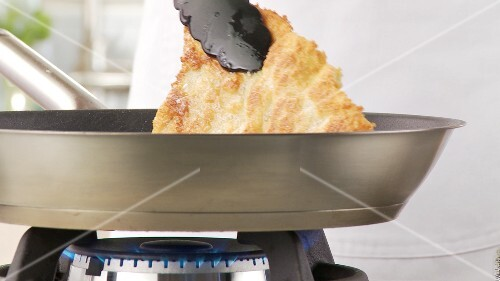 A breaded escalope being fried crispy in a pan