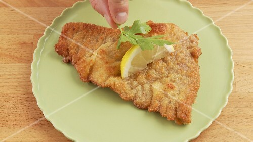 Escalope á la viennoise being garnished with a slice of lemon and a sprig of parsley