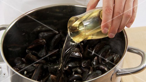 White wine being added to mussels