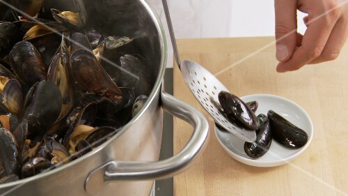 Closed mussels being removed from the pot