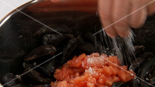 Tomato pieces being added to mussels and salted