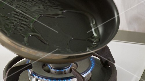 Vegetable oil being added to a pan and heated