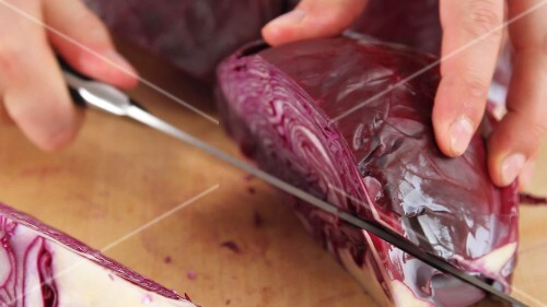 Red cabbage being quartered and the stem being removed