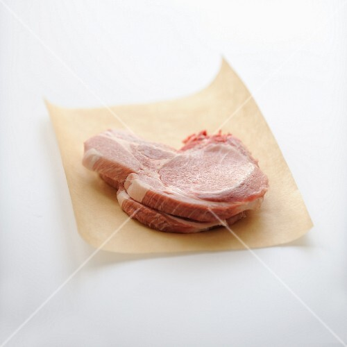 Raw pork chops on brown paper