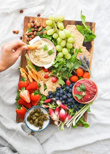 Red hummus and white hummus with a tray of crackers, fruit and raw vegetables to dip