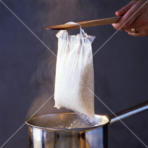 Lifting sachet of cooked rice from pan