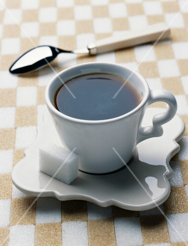 A cup of black coffee with a lump of sugar