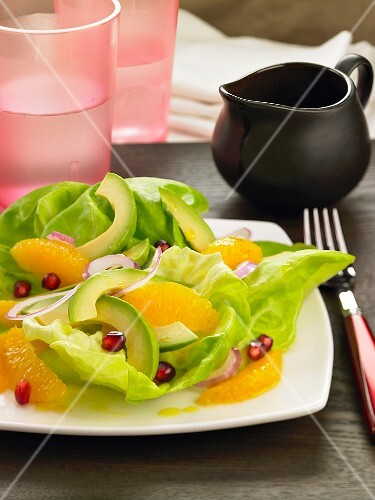 A green salad with avocado, oranges and pomegranate seeds