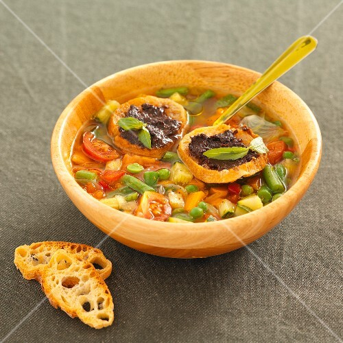 Summer vegetable soup with croutons and tapenade