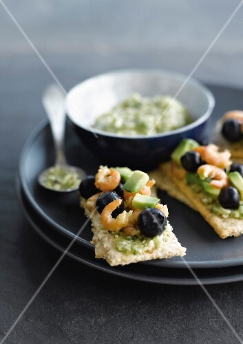 Guacamole, shrimps and bilberries on crackers