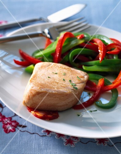 Thick piece of salmon with red and green peppers