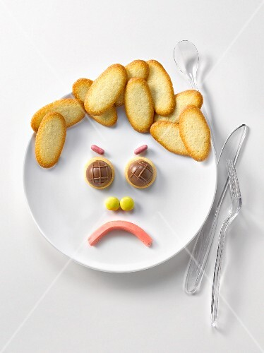 Plate of Langues de chat biscuits and candies in the shape of a sad face