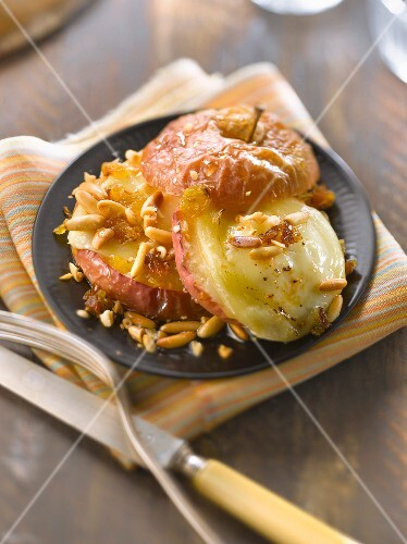 Baked apple with goat's cheese, honey, pinenuts and grapes
