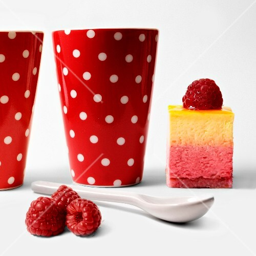 Piece of raspberry cake and two spotted cups