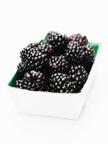 Punnet of blackberries on a white background