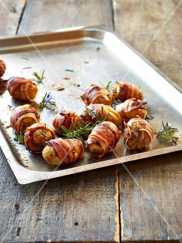 Baked potatoes wrapped in bacon with rosemary