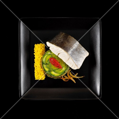 Steamed pike-perch,zucchinis and saffron rice on a black background
