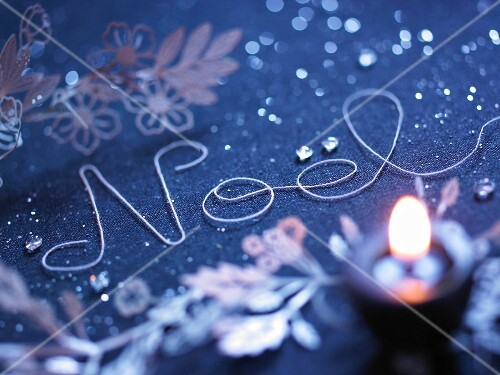 "The word ""Noel"" written with string on a Christmas decorated table"