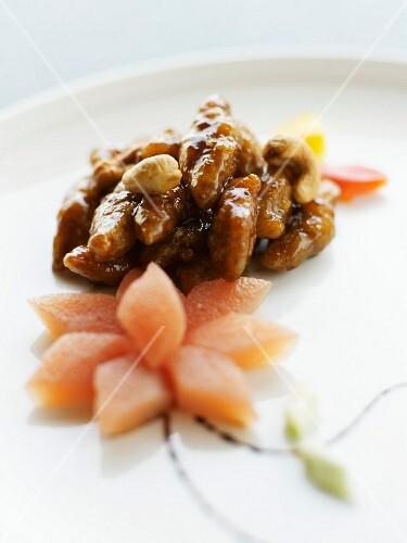 Pork with caramelized dried fruit, flower-shaped candied papaya