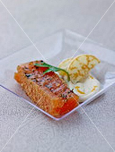 Piece of salmon in gingerbread crust,blinis with light orange-flavored cream