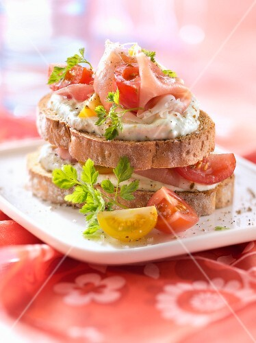 Goat's cheese,raw ham and tomatoes on toast