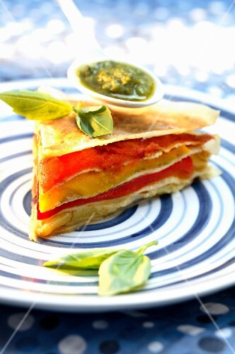 Slice of stewed red and yellow pepper,pesto and filo pastry layer