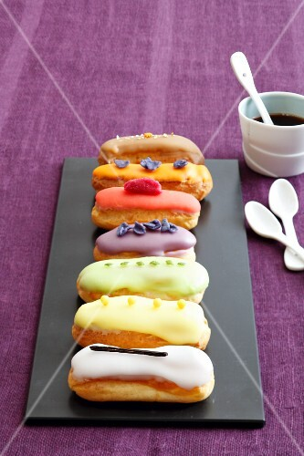 Various mini eclairs on a black platter