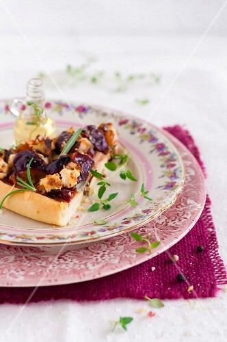 Slice of pizza with quetsch plum chutney and walnuts