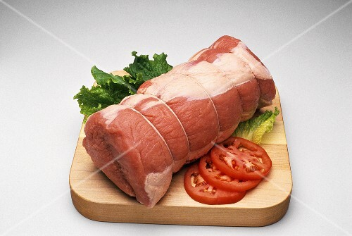 Large Roast on a Cutting Board; Tomato and Lettuce