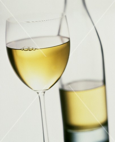A Glass of White Wine; Bottle in Background