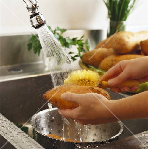 Hands Washing Sweet Potatoes in a Sink