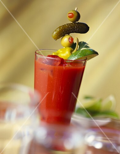 Bloody Mary with olive on cocktail stick and lime wedge