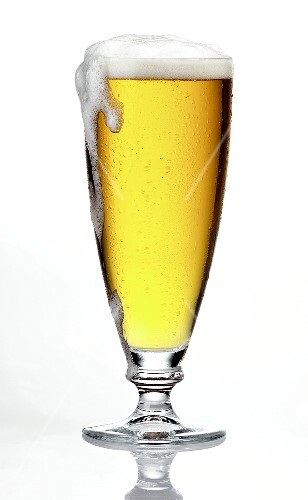 Glass of light beer, frothing over