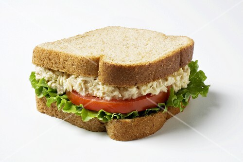 A Tuna salad sandwich with lettuce and tomato on whole wheatbread