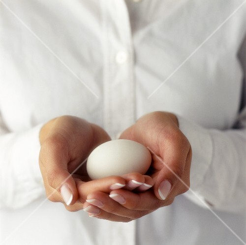 Hands Holding White Egg in Front of White Shirt