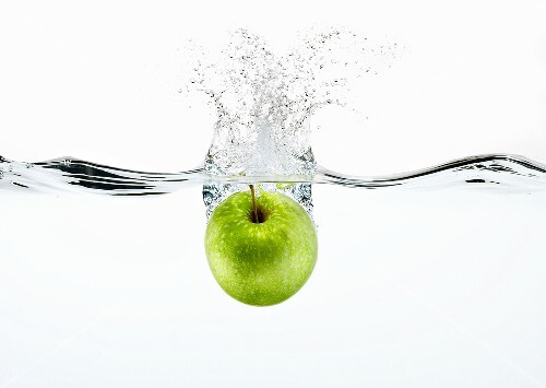 A Granny Smith Apple Splashing into Water