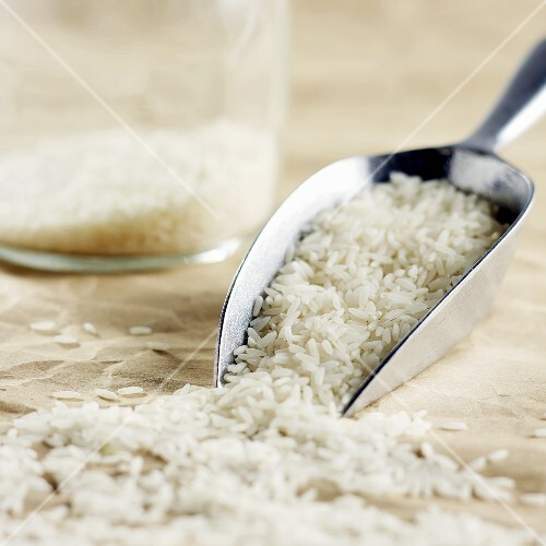Long-grain rice on metal scoop and in jar