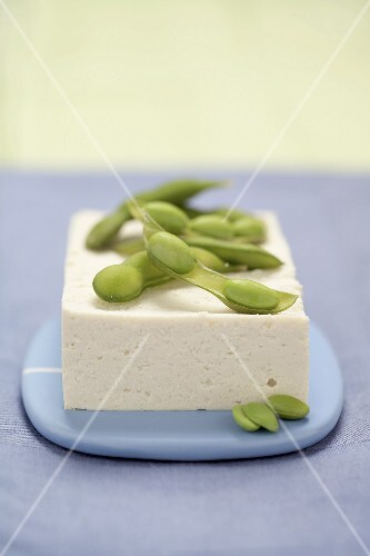 Green soya beans on a block of tofu