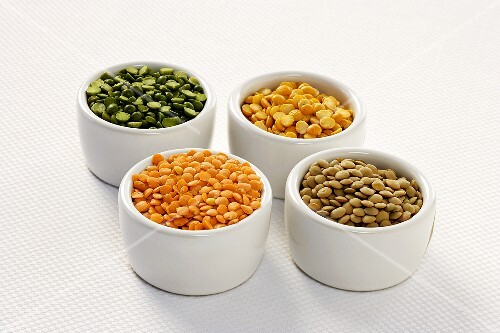 Four Small Bowls Full of Split Peas and Lentils; White Background