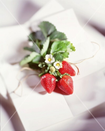 A bunch of three strawberries with flowers and leaves