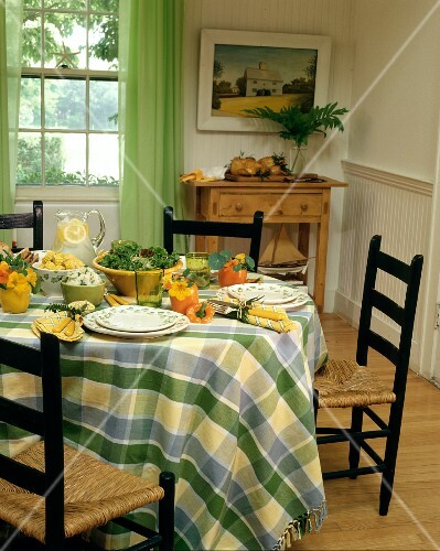 Country house table set in summery style with salad, corn