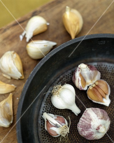 Various varieties of garlic in and beside pan