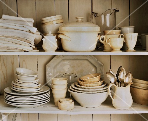 White tableware and table cloths on a kitchen shelf