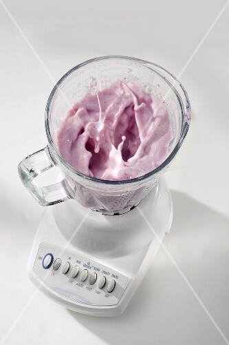 Berry Milk Shake Mixing in a Blender with No Cover, White Background
