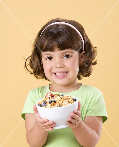 Little Girl Holding Bowl of Cereal with Fruit