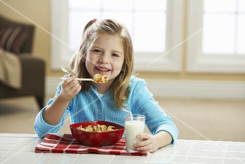 Little Girl Eating a Bowl of Pasta for Lunch; With Milk